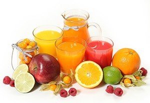 sweet juice and fruits on white